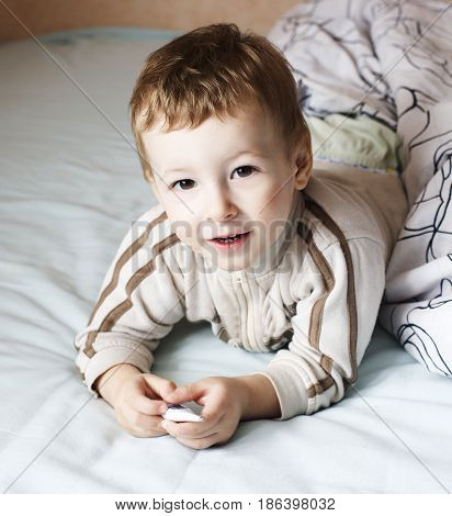 little cute boy in bed , lifestyle people concept close up