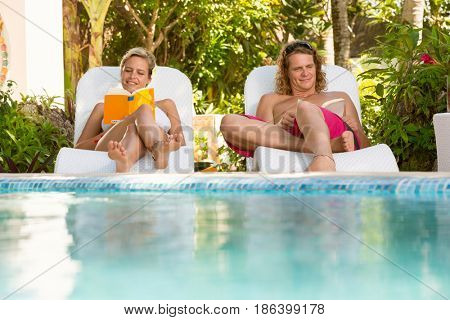 Couple relaxing together in sunbed . Romantic young couple lying in sunbed resting and reading book
