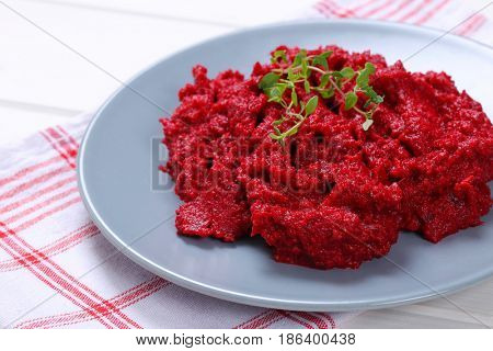 plate of fresh beetroot puree on checkered dishtowel - close up