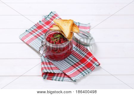 jar of fresh beetroot puree with toasts on checkered dishtowel