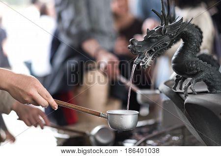 etal dragon spewing water in the well in the Senso-ji temple Tokyo Japan.