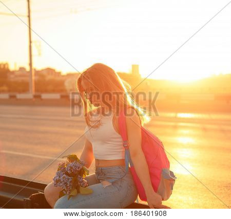 Young attractive hipster girl hitchhiking sits on the highway fence and holds a bouquet of lilac flowers. She is dressed in top and jeans. Backlight photography. Road Trip