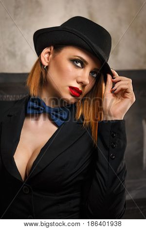 Young attractive girl in a jacket bow tie and bowler hat. Femme fatale. Evening makeup smokey eye. She looks past.