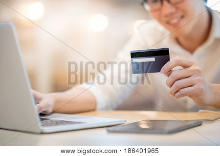Man hand holding credit card see the security code and using laptop computer for online shopping and online payment modern lifestyle with digital transaction concepts