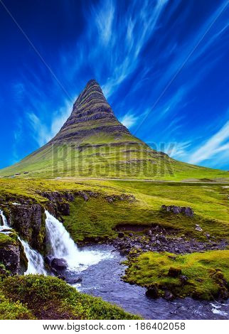 The famous mountain in Iceland is Kirkufell. At the foot of the mountain cascading waterfalls Kirkjoufellfoss. Cirrus clouds in the blue sky. The concept of exotic and extreme tourism