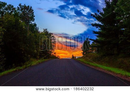 Blacktop road headed for a colorful Wisconsin sunset