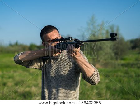 The man takes aim at the target with a sniper strikeball rifle. Selective Focus