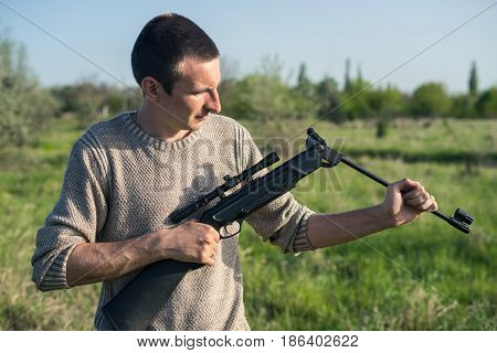 Closeup view of man recharges sniper rifle outdoor. Selective Focus. Green grass and blue sky on background