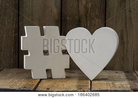 Decorative 3D Paper Hash And Heart Over Wooden Background