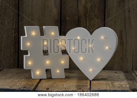 Illuminated Decorative Hash And Heart Sign Over Wooden Background