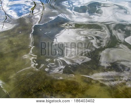 Abstract beige blue water background. Through the water you can see the sandy bottom with algae And the reflection of the sky on the surface