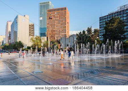Mexico City, Mexico - April 20, 2017: Children playing at the fountain show at the Monument to the Mexican Revolution (Monumento a la Revolución) located in Republic Square, Mexico City