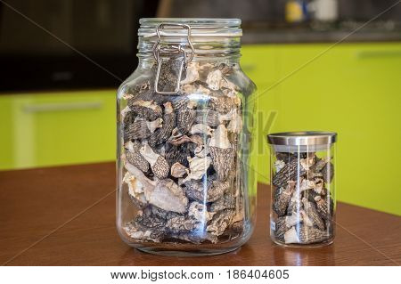 Dried morels - great edible mushrooms - in glasses on wooden table in kitchen
