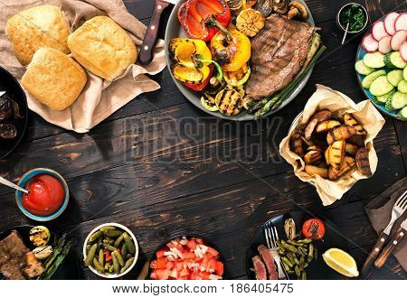 Outdoors Food Concept. Frame of Different foods cooked on the grill on the wooden table grilled steak and grilled vegetables. Top view