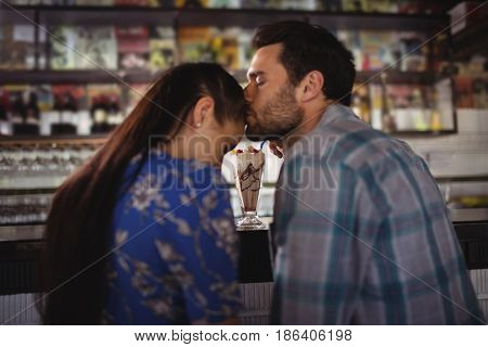Affectionate man kissing woman at counter in restaurant