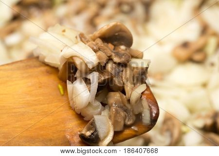 Mushrooms with onions are fried in a frying pan .