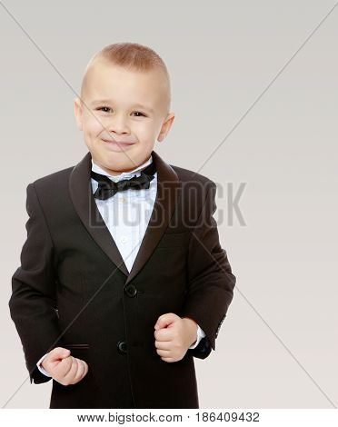 Beautiful little blond boy in a fashionable black suit with a tie. The boy tightly clenched his fists. On a gray background.