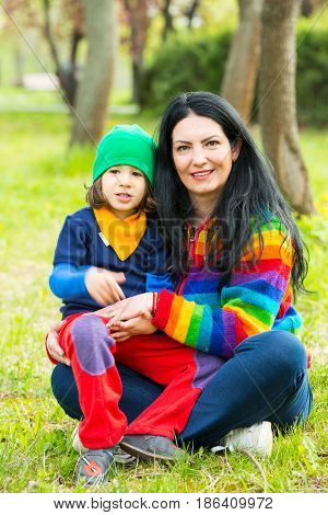 Cheerful mom and son sitting on grass iin park