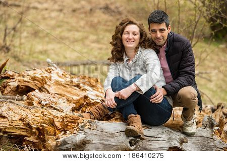 Cheerful middle aged couple sitting on a bark tree outdoor