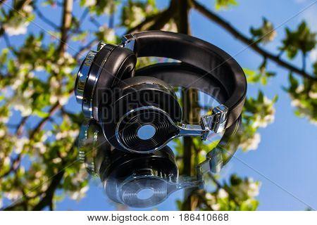 black wireless travel headphones on mirror background