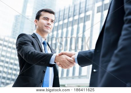Businessmen making handshake in front of office buildings in the city - greeting dealing merger and acquisition concepts