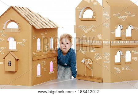 Pretty little blonde girl in a blue shirt peeks out from behind the cardboard house.