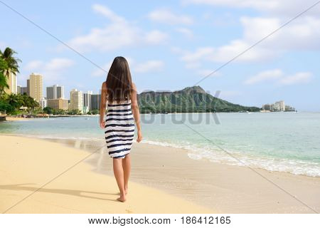 Waikiki beach vacation woman relaxing walking on sand at sunset. Honolulu travel destination in Oahu, Hawaii.