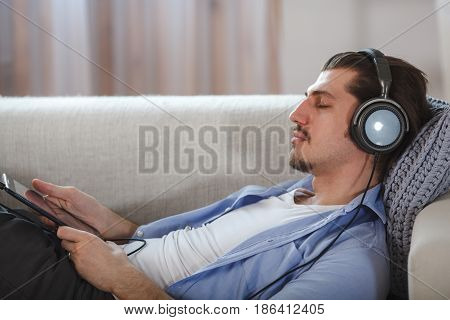 Handsome bearded guy lying with closed eyes on sofa with tablet and headphones