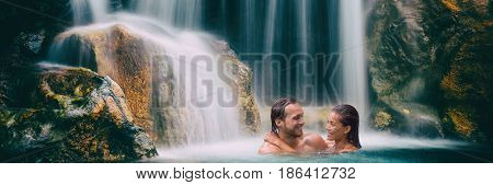 Waterfall couple relaxing in nature banner. Panoramic crop of people swimming in natural pool in tropical nature forest, Romantic travel vacation.