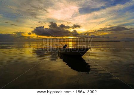 Fishing boat against colorful sky with clouds and refelction in the sea during low tide beach at sunrise in Labuan island,Malaysia.Nature background.