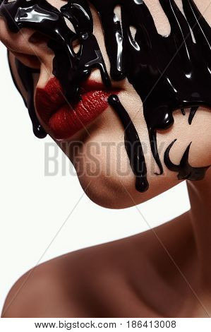 Face of Woman with black fluid Paint and red Lips
