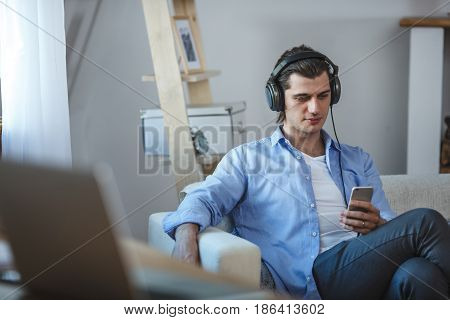 Handsome guy looking to the smartphone screen sitting on sofa in corner of room near window