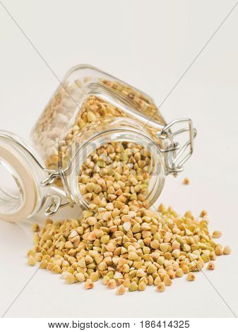 Raw green buckwheat in bank on white background. Vertical. Copy space. Healthy food and diet concept