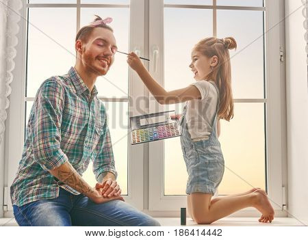 Funny time! Father and his child are playing at home. Cute girl is doing makeup to her dad, sitting on the window in the room. Family holiday and togetherness.
