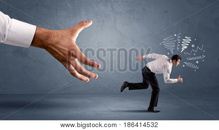 Stressful businessman running from a big hand concept on background