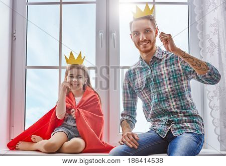 Happy father's day! Dad and his child daughter are playing and having fun together. Beautiful funny girl and daddy have crowns on sticks. Family holidays and togetherness.