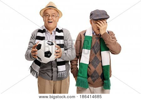 Two elderly football fans with one of them cheering and the other holding his head in disbelief isolated on white background