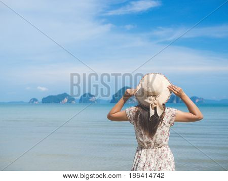 black and white of sad Woman in summer vacation wearing straw hat and beach dress looking the view at the ocean