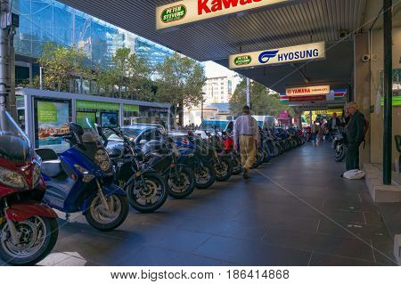 People Walking Street Past Scooters And Motorcycles Display