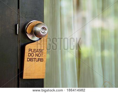 Signboard do not disturb hanging on open door in a hotel