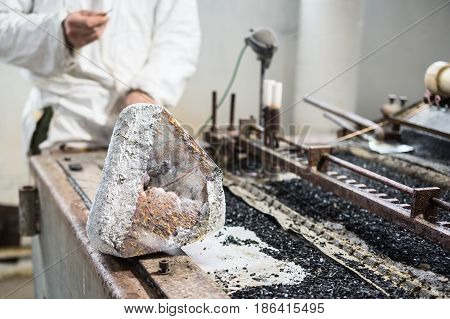 Industrial tinning of wire. A large piece of tin solder lies on the edge of the tin bath.