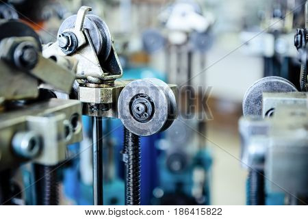 Equipment for making braids from metal wire. Selective focus. Elements of the mechanism of the braiding machine. Close-up rollers, wheels, guide elements.