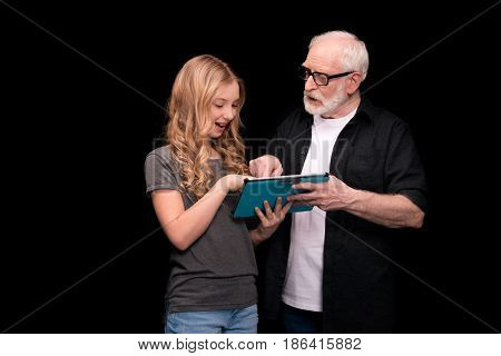 Grandfather And Granddaughter With Digital Tablet