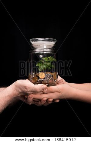 Grandfather And Granddaughter With Coins And Plant In Jar