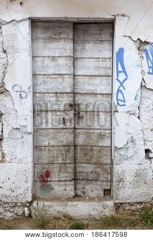 very old wooden doors with padlock in derelict building with cracked walls in greece