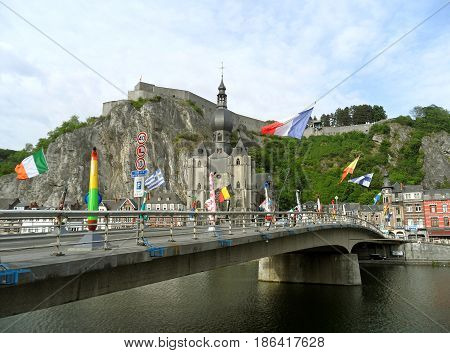 Charles-de-Gaulle Bridge with many giant saxophone sculptures and the Collegiate Church of Notre-Dame in Background, Dinant, Wallonia, Belgium