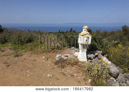 miniature chapel on roadside in mani part of peloponnese in greece with blue sea and sky in the background