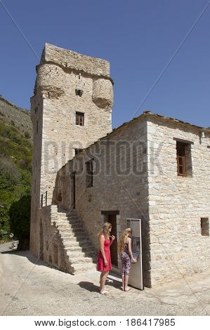 kastania greece 28 april 2017: tourists look at map near old tower in old greek village kastania on peloponnese