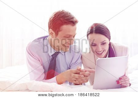 Happy business couple using digital tablet in hotel room