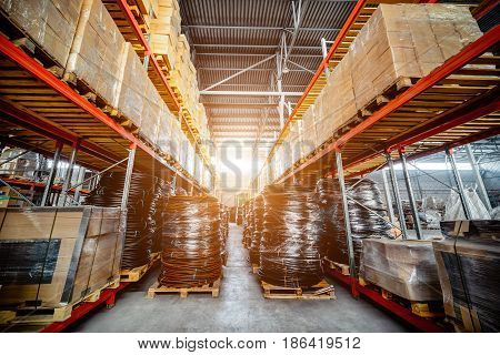 Warehouse transport and freight company. In the foreground a pile of cardboard boxes and a coil of plastic tubing. Toning the image. Bright sunlight.